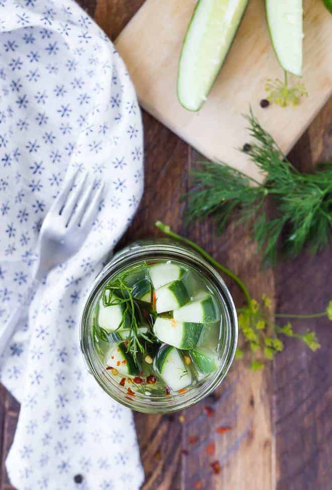 Overhead of pickles in jar, with fork, cloth, fresh dill and sliced cucumbers arranged around.
