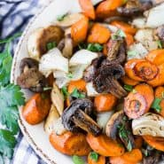 Image of balsamic roasted vegetables in a bowl, garnished with fresh flat leaf parsley.