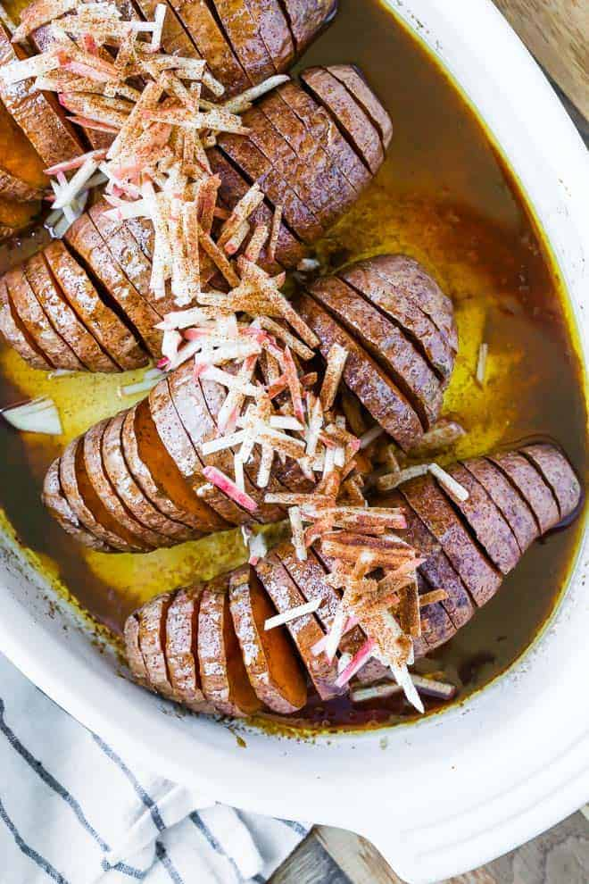 Image of sweet potatoes cut in a hasselback style and baked with cinnamon and butter.