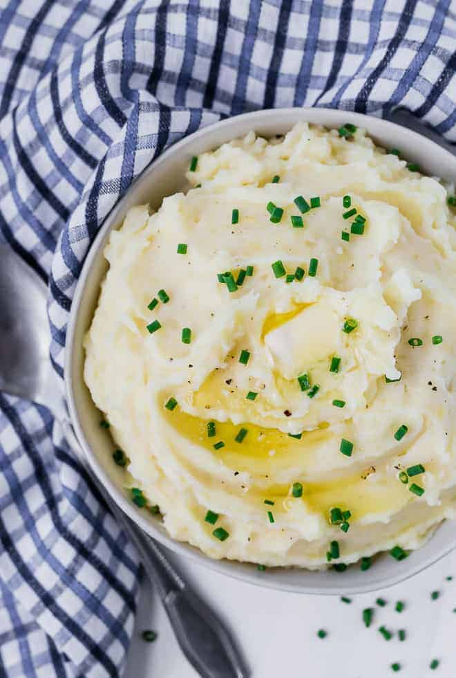 Image of creamy mashed potatoes in a bowl topped with melting butter and chives.