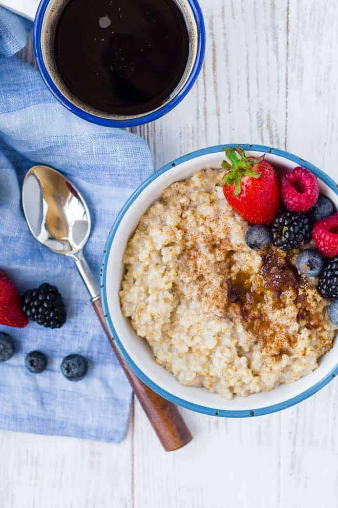 Photograph of pressure cooker steel coat oats, topped with berries. A spoon and a cup of coffee are also pictured.