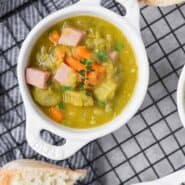 Image of split pea soup recipe with ham, carrots, and thyme. In a small white crock with bread next to it.