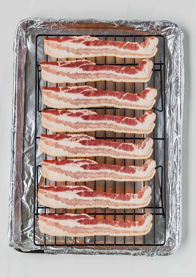 image of raw bacon on a baking rack on top of a sheet pan.