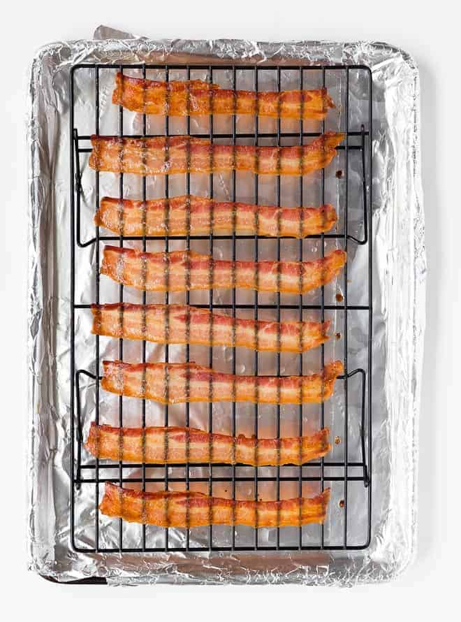 Image of crispy cooked bacon on a baking rack on a sheet pan.