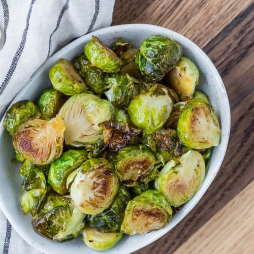 Brussels sprouts roasted, in a bowl, overhead image on a wooden background.
