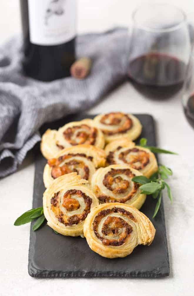 Puff pastry pinwheels on a slate board with fresh sage. Red wine in background.