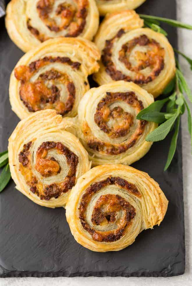 Pinwheels made with puff pastry, sausage, apple, cheese, and sage. Arranged on black slate.