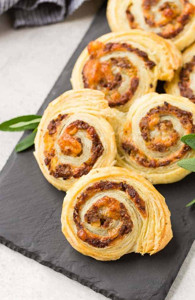 Sausage pinwheels made with puff pastry on a black slate board.