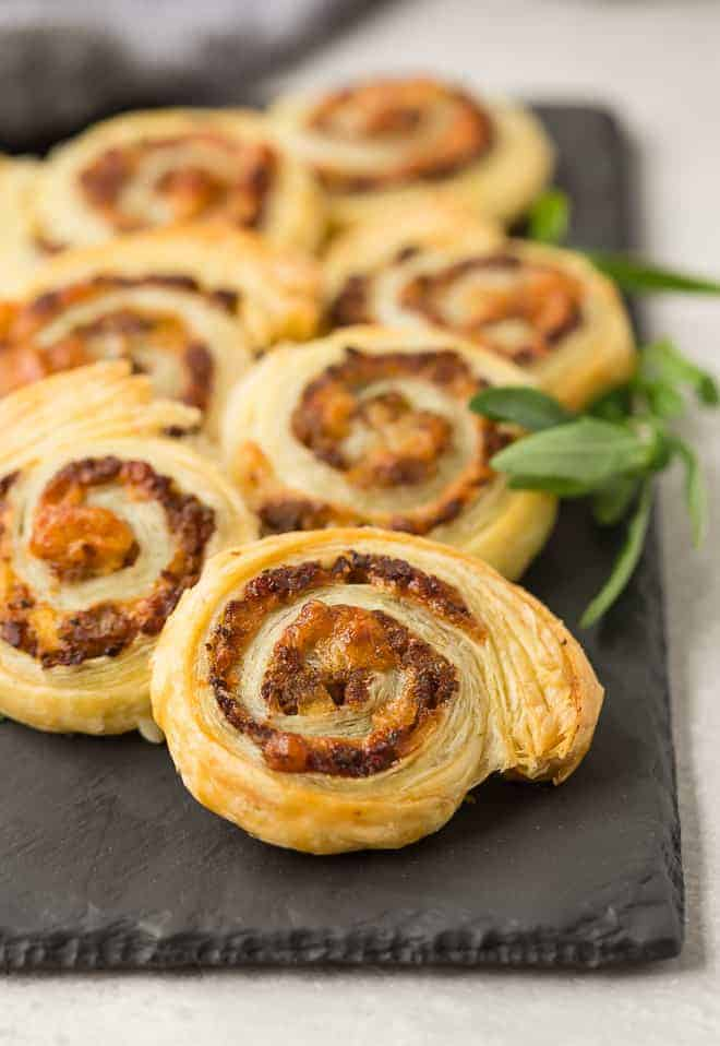 Pinwheel appetizers made with sausage and apple on a black slate board.