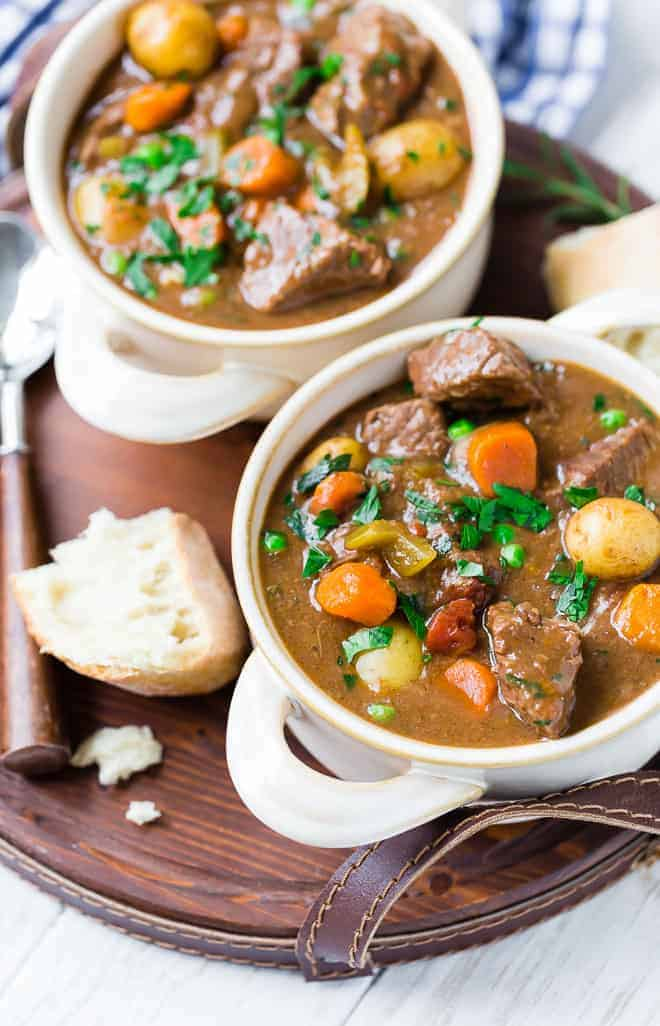 Image of cozy slow cooker beef stew in two bowls, served on a tray with bread and two spoons.