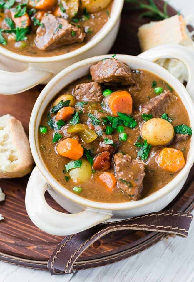 Image of a bowl of stew with beef, potatoes, carrots, celery, and garnished with parsley. Served with bread.