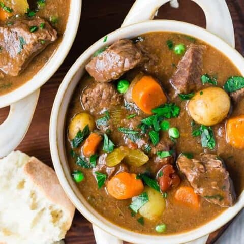 Image of crockpot beef stew in a white bowl with two handles. The beef stew is garnished with parsley and served with bread.