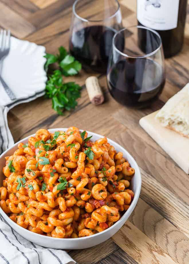 A large white bowl full with curly pasta coated in a tomato sauce. Also pictured are bread, red wine, wine cork, fresh parsley.