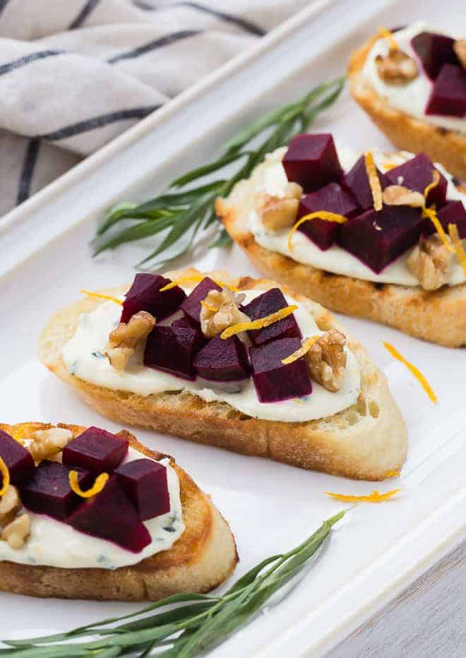 Close up image of beet crostini on a white platter.