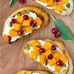 Image of butternut squash crostini topped with pomegranate and pepitas.