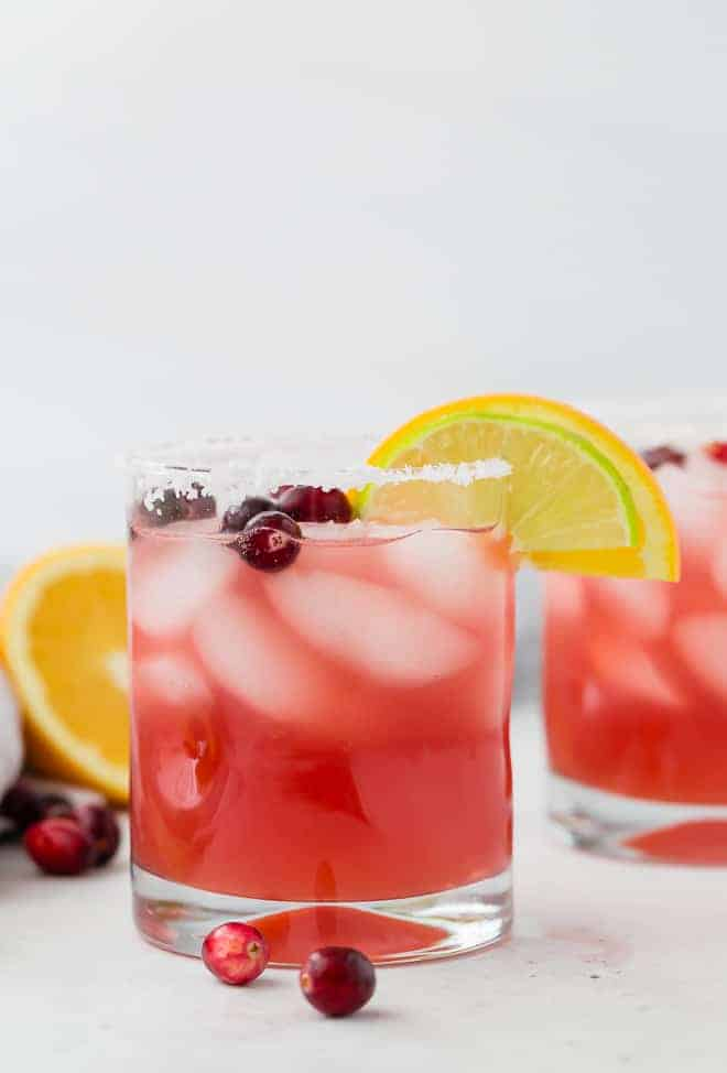 image of a cranberry margarita with orange and lime, garnished with fresh cranberries.