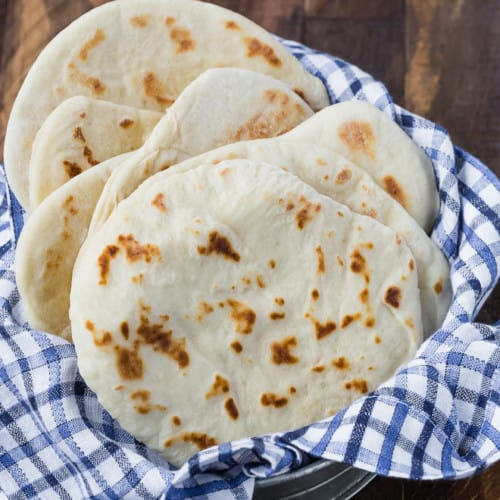 6 pieces of flatbread in a metal basket with a blue and white towel. Wood background.