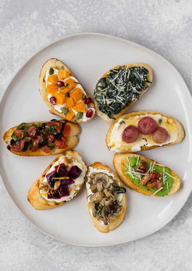 Image of 7 different types of crostini, arranged in a circle. Learn how to make crostini in this comprehensive guide.