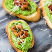 Image of pea crostini on a black marble serving platter, topped with pancetta and parmesan.