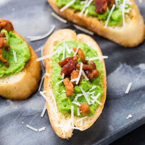 Image of creamy pea puree spread on crispy bread slices, topped with pancetta and parmesan.