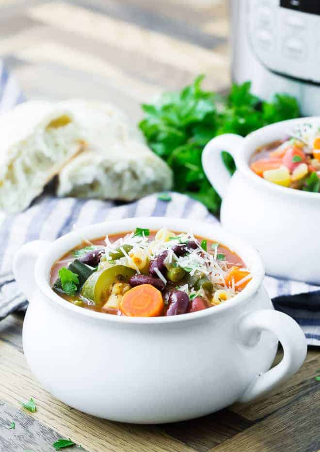 Image of minestrone soup in a white bowl.