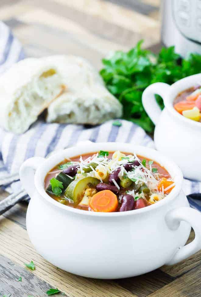 Image of pressure cooker minestrone in a bowl. Another bowl, parsley, bread, and an Instant Pot are in the background.
