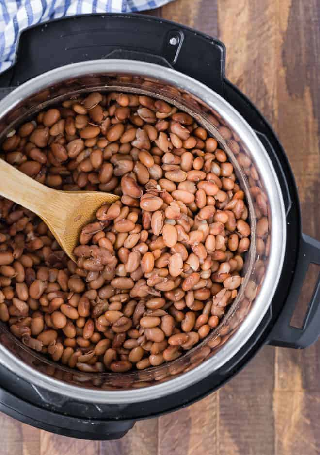 Image of cooked pinto beans in an instant pot with a wooden spoon on a wooden background.