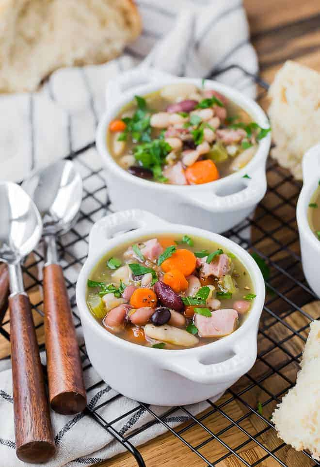 Ham bone soup with 15 beans, in three small white bowls. Bread and spoons are also pictured.