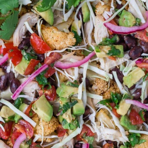 Image of roasted cauliflower topped with an assortment of southwestern flavors: pickled red onions, tomatoes, cabbage, avocado, black beans, and shredded cheese.