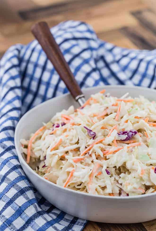 Creamy coleslaw in a bowl, with a wooden spoon inserted into the coleslaw.