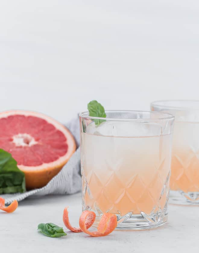 Image of a pale pink grapefruit cocktail with a half of a grapefruit in the background, also basil leaves are pictured.
