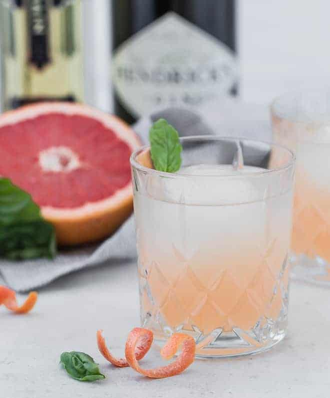Image of a pale pink cocktail, garnished with a fresh basil leaf. Hendricks Gin and elderflower liqueur are pictured in the background. A curl of grapefruit rind is in the foreground of the photograph.