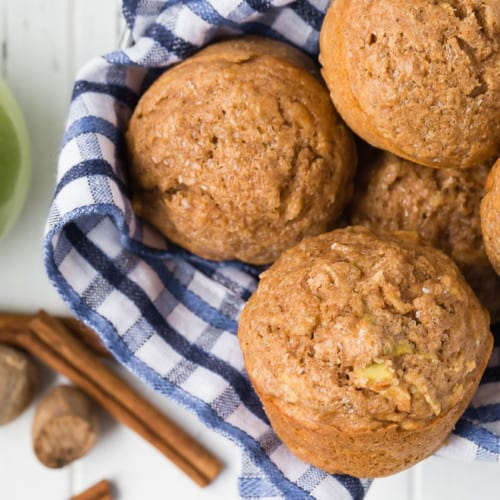 Healthy apple muffins in a basket with a blue checkered towel.