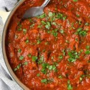 Image of a large pot of homemade spaghetti sauce with a spoon in it. It is garnished with lots of chopped fresh parsley.
