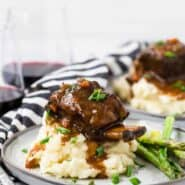 Image of a short rib on top of a pile of creamy mashed potatoes with brown gravy dripping down them. Everything is garnished with fresh chives.