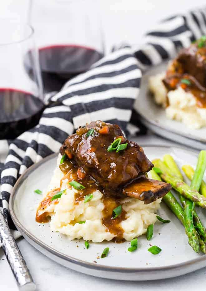 Image of Instant Pot short ribs on a pile of mashed potatoes, garnished with fresh chives. Short ribs are served with sauteed asparagus and a glass of red wine.