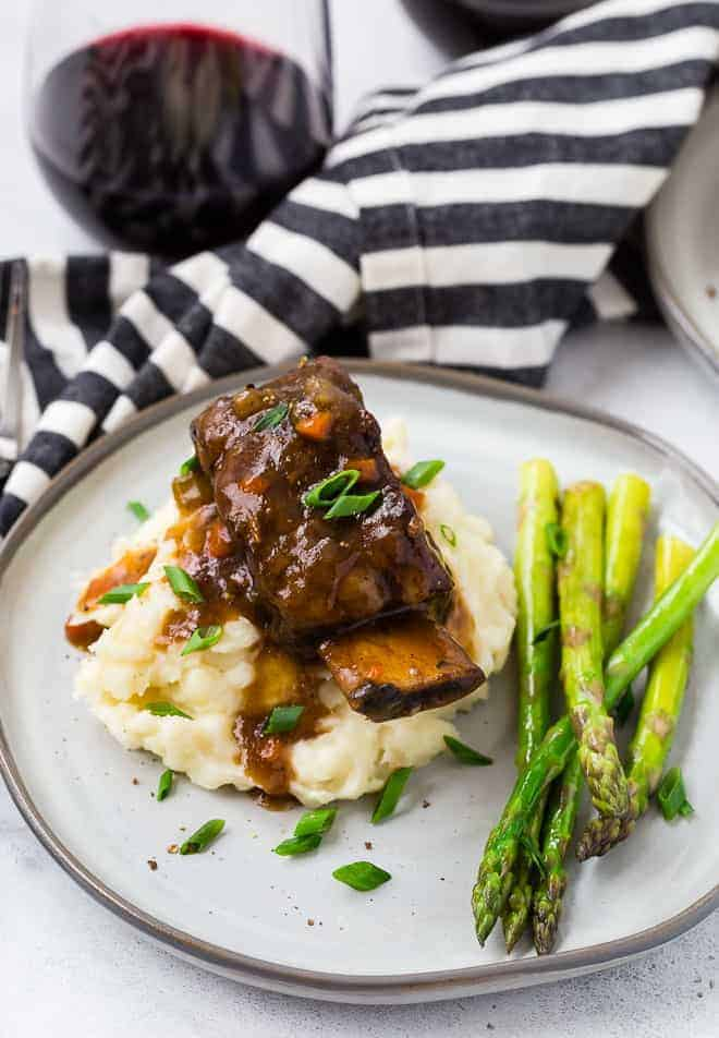 Image of short ribs cooked in an instant pot pressure cooker. Asparagus, mashed potatoes, and red wine are also pictured.