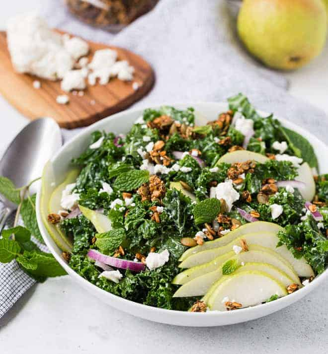 Vibrant green kale salad topped with red onions, pears, and savory granola.