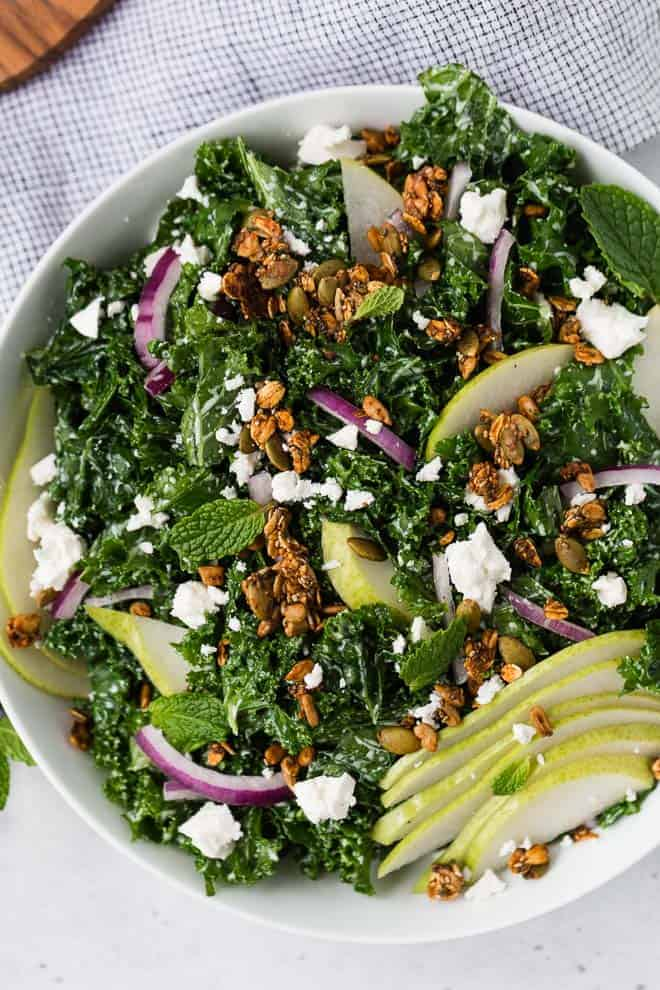 Image of kale and pear salad in a white bowl topped with onions, feta cheese, and savory granola.