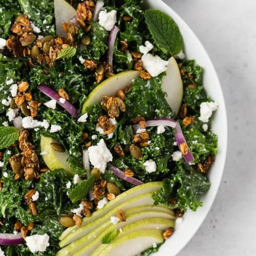 Image of a kale salad in a white bowl topped with pears, feta cheese, red onions, and savory granola.