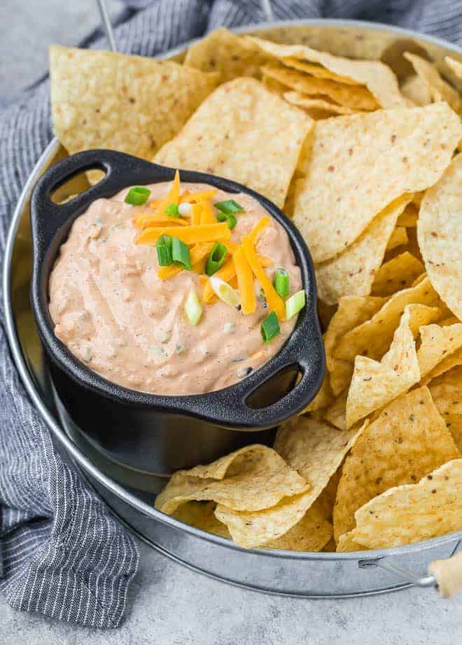 Image of mexicali dip in a black bowl with two handles. Dip is surrounded by chips on a tray.