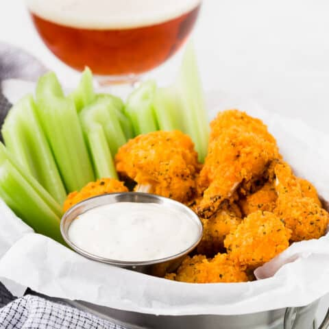 Image of air fried buffalo cauliflower bites with a beer in the background.