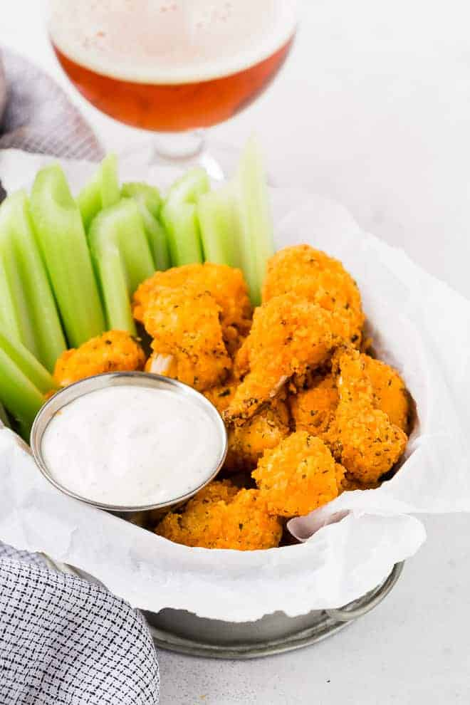 Image of breaded cauliflower bites seasoned with buffalo wing sauce. They are placed in a basket with celery sticks and ranch dressing. A glass of cold beer is in the background of the image.
