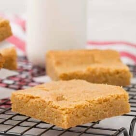 Image of easy, rich blondies on a cooling rack with milk in the background.