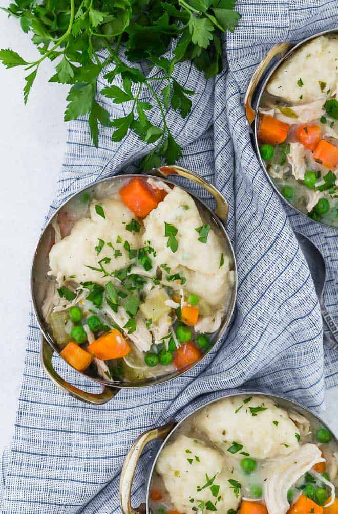 Image of three bowls of chicken and dumplings, garnished with fresh parsley.