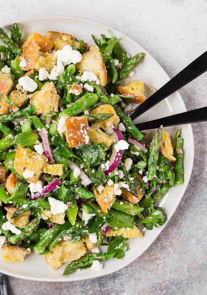 Image of a fresh green spring salad made with asparagus, croutons, red onions, mint, and parsley.