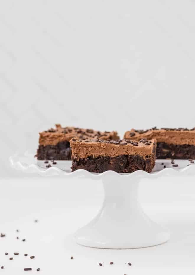 Chocolate brownies flavored with espresso powder on a white cake stand.