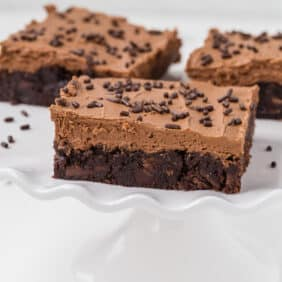 Mocha brownies with frosting, on a cake stand.