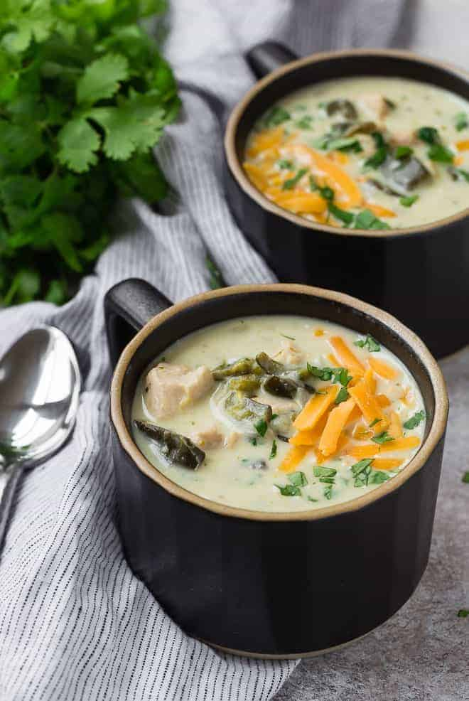 Creamy soup in two black mugs, topped with cheddar cheese and cilantro.