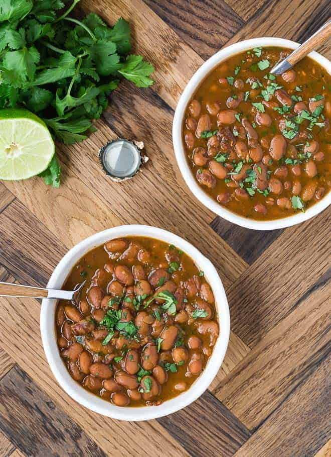 Image of two bowls of soupy pinto beans that have been cooked with mexican flavors.